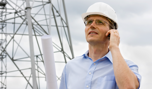 Man in hardhat on phone in front of tower