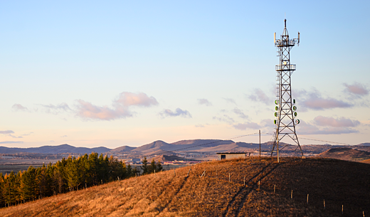 Tower in brown wheat field with mountains behind